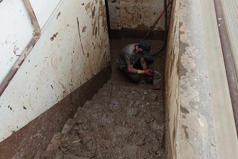 Mann reinigt Treppe von Schlamm