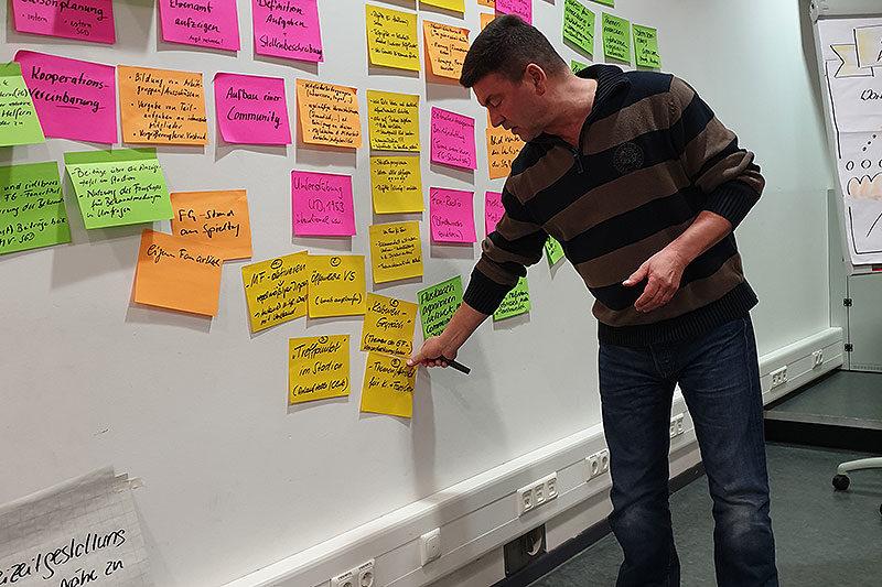 Andreas klebt Zettel an Wand